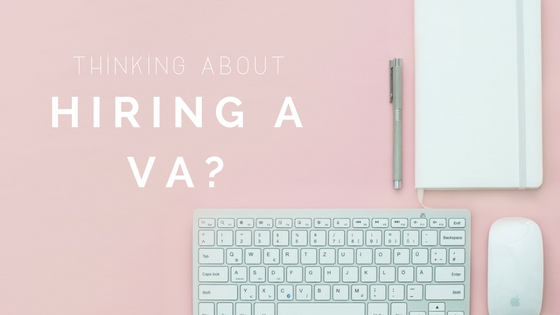 Baby Pink Background with white apple mouse, keyboard, notebook and pen 'Thinking about hiring a VA?'