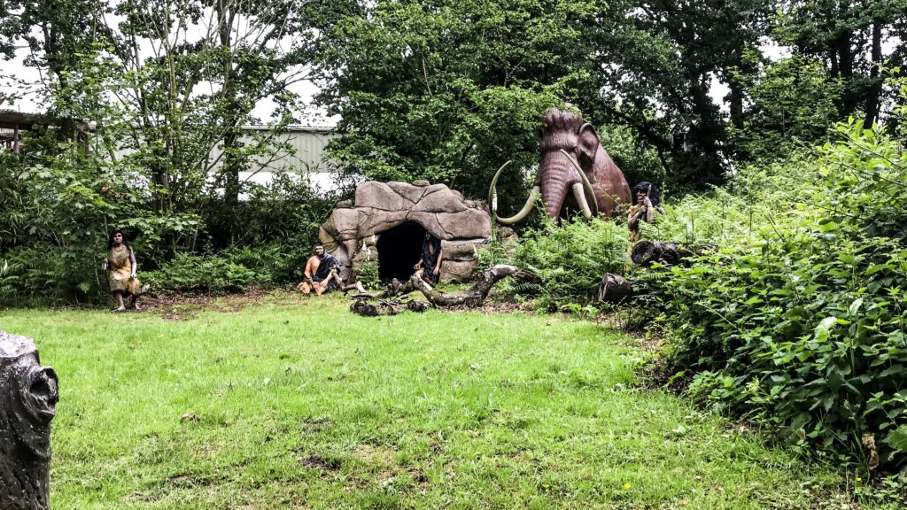 Neanderthals in their home cave with a Wooly Mammoth standing close behind on Neanderthal walk at Roarr Dinosaur Adventure