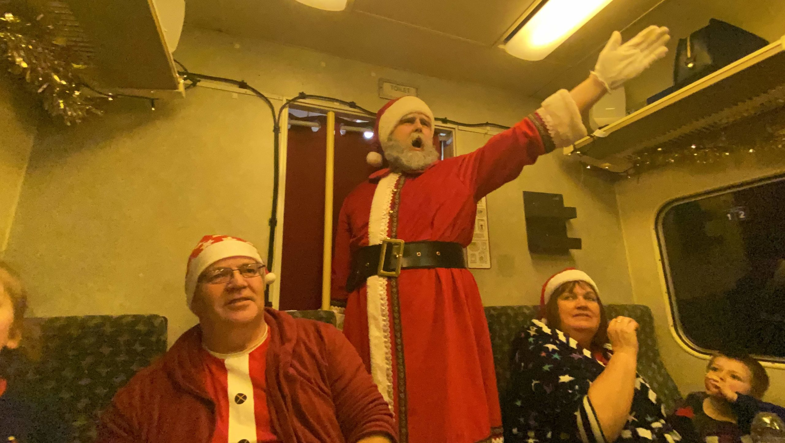 Santa visiting and giving the first gift of Christmas - a silver bell on the polar express