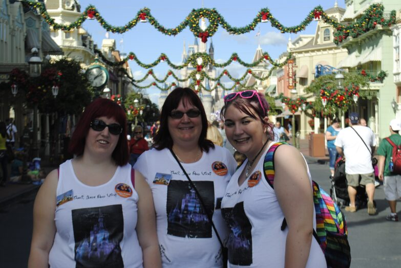 3 adults stand on Main Street at Magic Kingdom in Walt Disney World. Surrounded by Christmas decor.